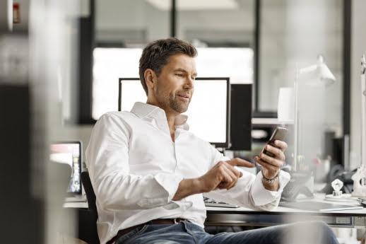 biznesmen uzywa aplikacji mobilnych do zbierania tresci